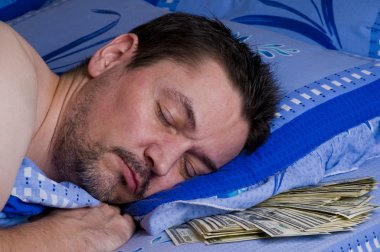 Man with money under his pillow