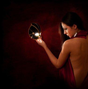 Beautiful woman looking at a magic mask