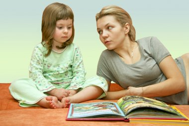 Mum reads a fairy tale to the child