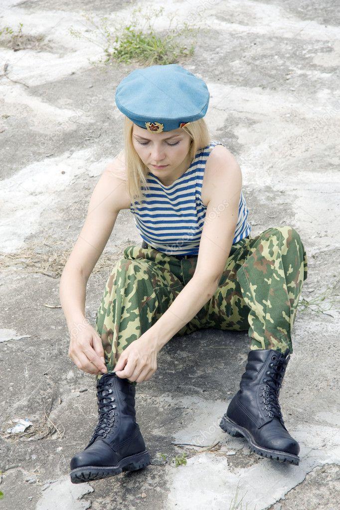 девушка в военной форме села на корточки доме