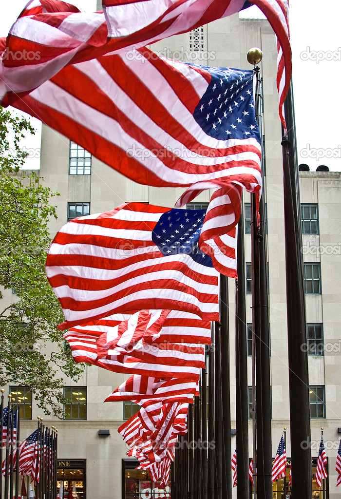 Wind is blowing through a row of American flags at the Rockefeller Center in New York City