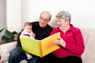 Grandparents reading book to baby girl.