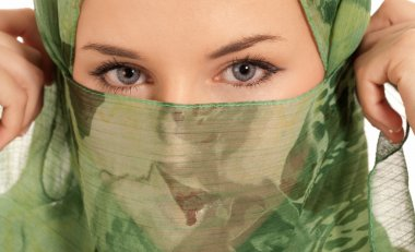 Young arab woman with veil showing her eyes isolated on white background
