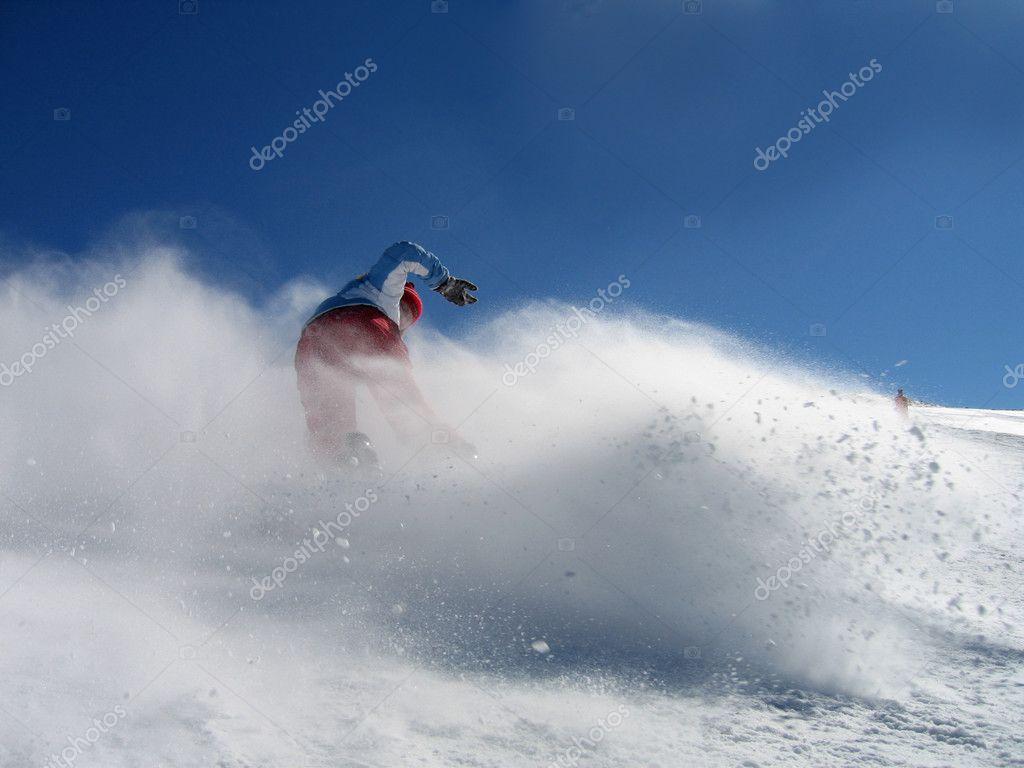 Girl snowboarding in powder snow
