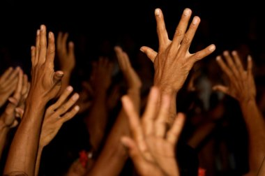 Raised hands on black background