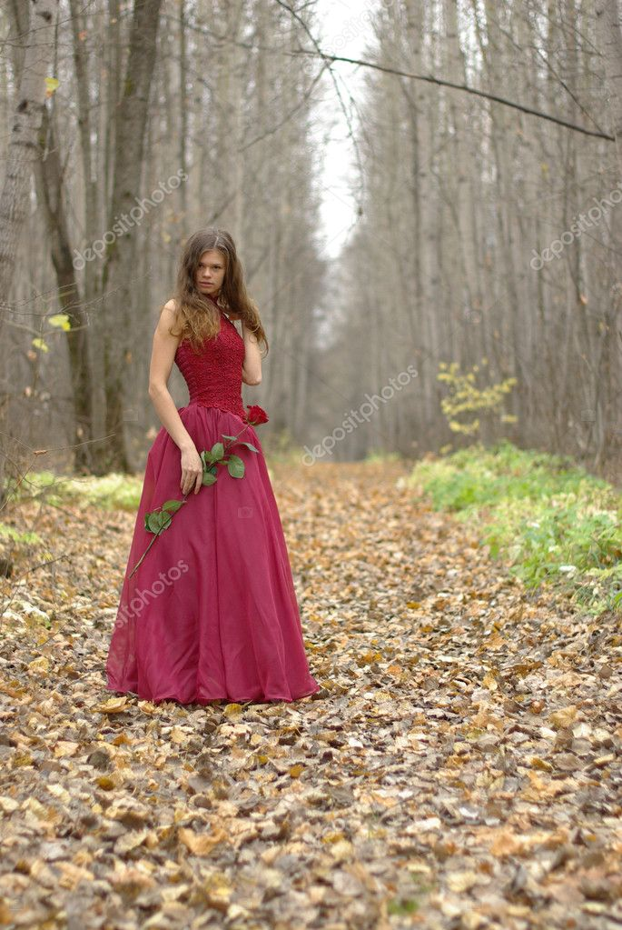 Girl with a rose in the forest