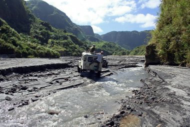 Adventure driving off-road vehicles fording river to mount pinatubo