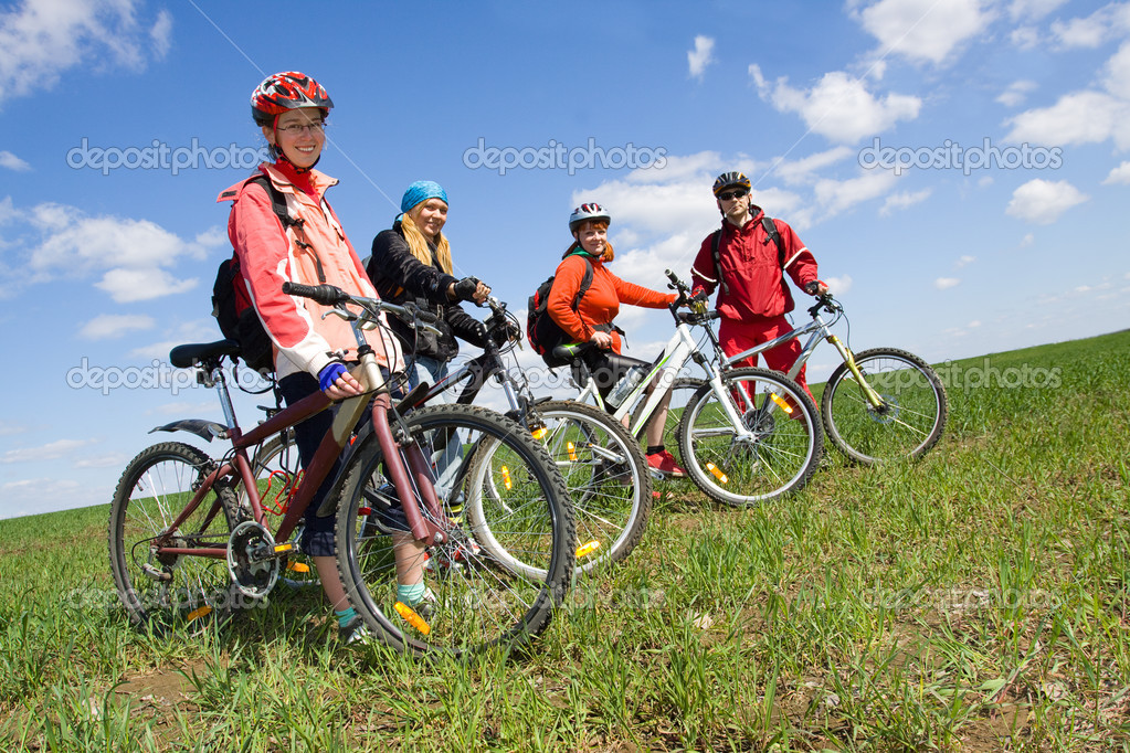 A group of four adults on bicycles in the countryside