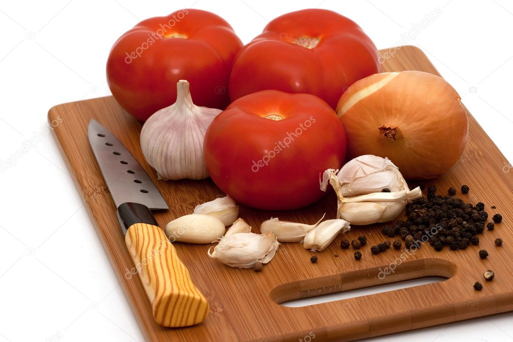 Tomatoes garlic onion black paper knife on wooden board