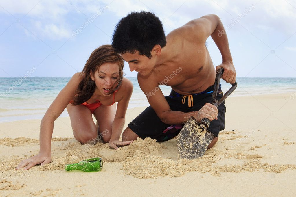Couple on the beach in hawaii digging