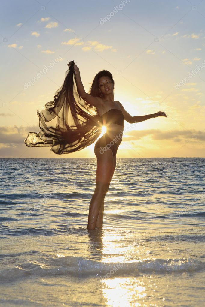Black female dancer standing in the ocean