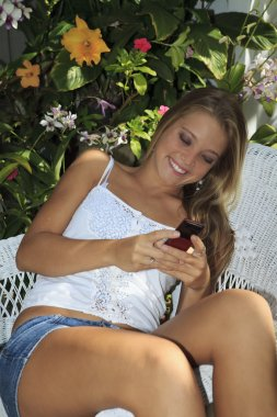 Beautiful teenage girl texting on her cell phone