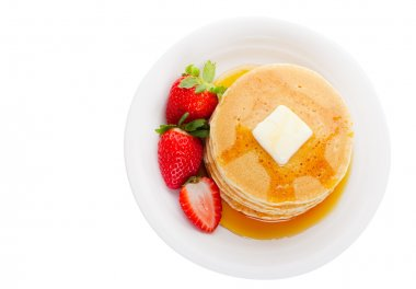 Plate full of fluffy golden pancakes with strawberries and maple syrup in overhead view stock vector