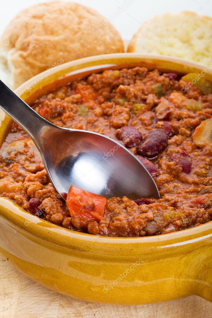 Bowl of chili with crusty buns and spoon