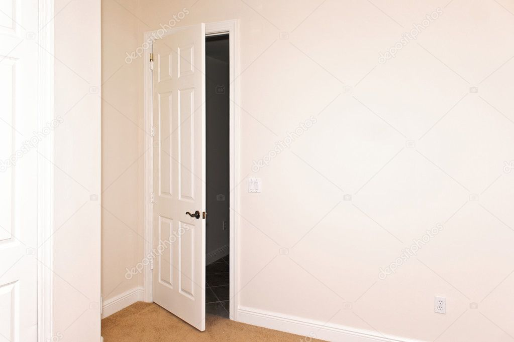 A white door is slightly open beside a big blank wall with copy space \u2014 Photo by sorsillo & Room with door ajar \u2014 Stock Photo © sorsillo #3099941