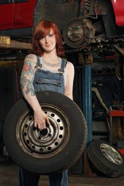 Female mechanic changing tires