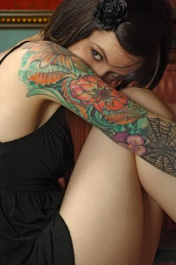 Shy female with tattoo