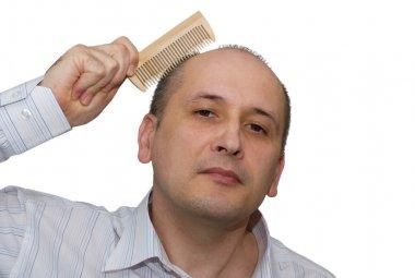 Bald man combs hair