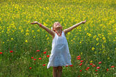ragazza circondata da fiori di colza
