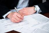 Obchodní muži vyplňování některých dokumentů