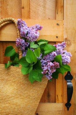 Lilacs in a straw purse