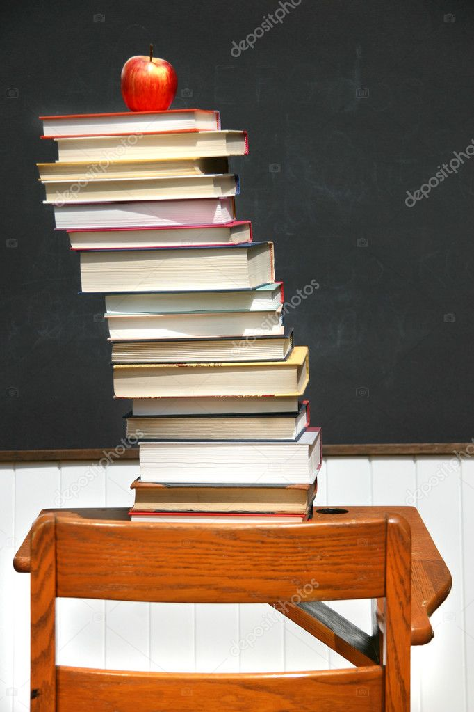 Stack of books on an old school desk