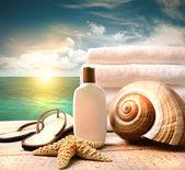 Fotografie Sunblock lotion and towels and ocean scene