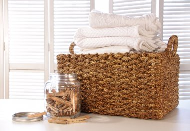 Laundry basket with linens on table