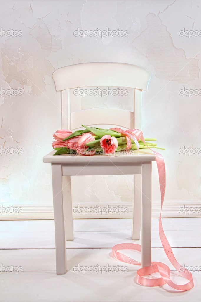 Little white chair with pink tulips