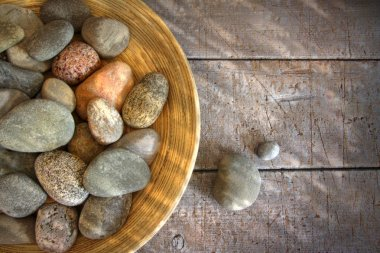 Spa rocks in wooden bowl on rustic wood
