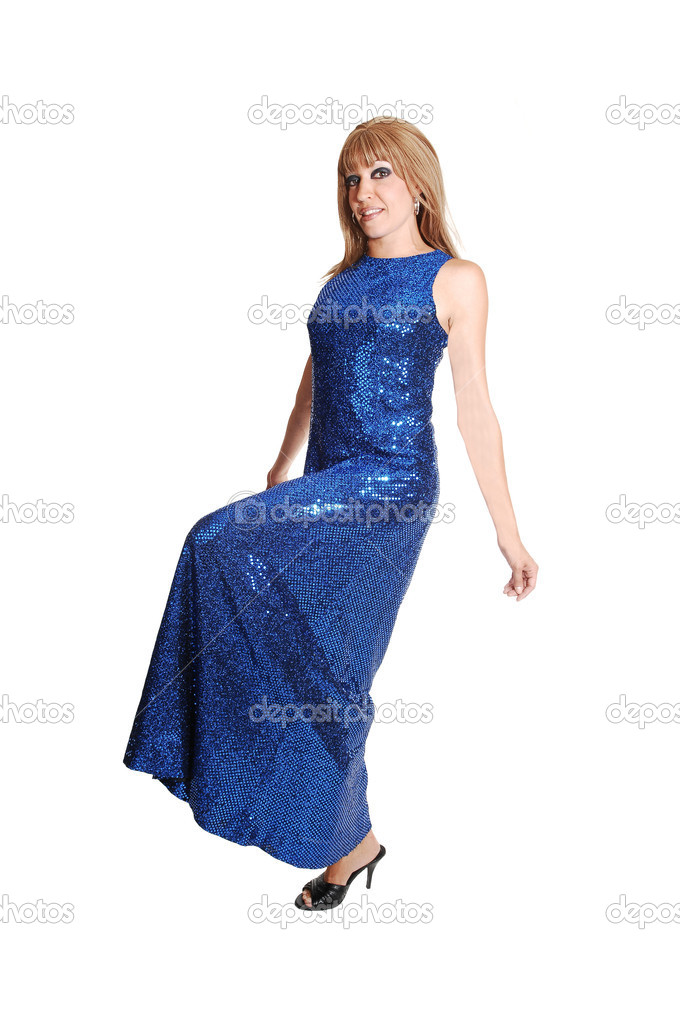 398234be2 A brunette young pretty woman in a long navy blue dress standing in the  studio looking shy into the camera on white background.