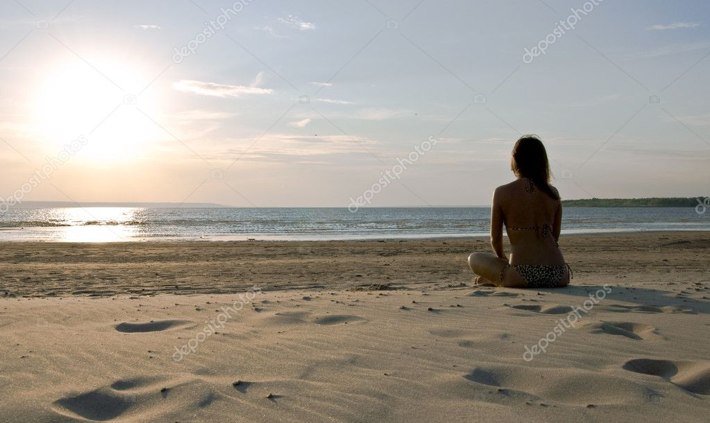 Young girl sitting on a deserted beach