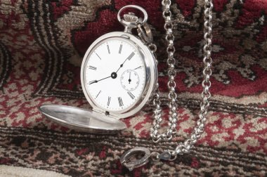 Silver pocket watch on carpet