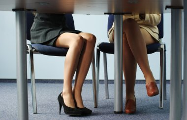 Legs of women under table