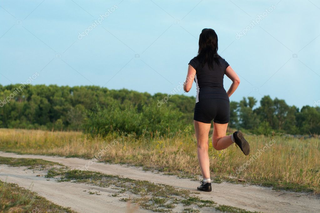 Woman jogging outdoors on the meadow