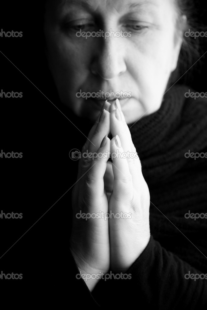 Woman praying or deep in thoughts, special black and white film-looking photo f/x,focus on hands (nearest fingers) stock vector