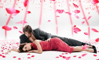 Attractive couple over falling rose petals