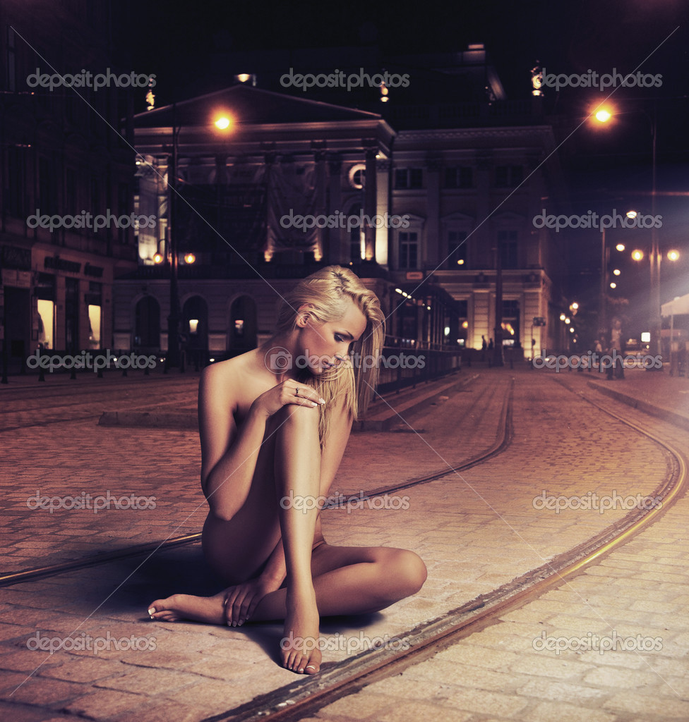 Naked young woman in sensual pose on the street
