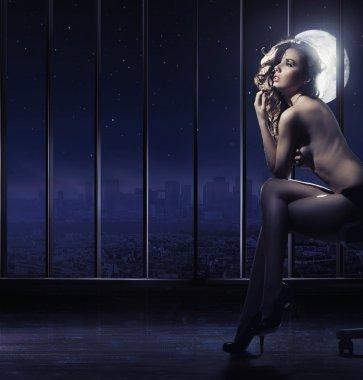 Naked brunette beauty posing at full moon