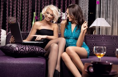 Young pretty girls sitting on the sofa and watching something on