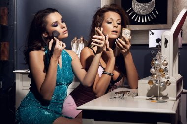 Two young beauty doing make up and preparing for the party