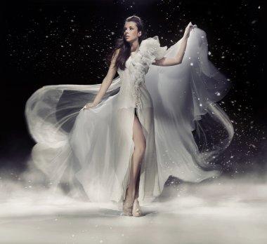 Sensual brunette woman dancing in white dress