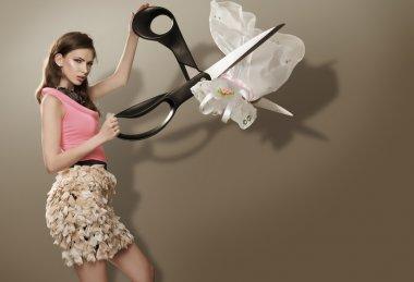 Beautiful young girl slashing wedding dress