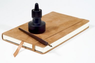 Isolated quill pen,ink bottle and suede-coverd journal.