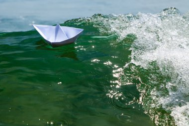 Paper boat struggling with a huge foamy waves