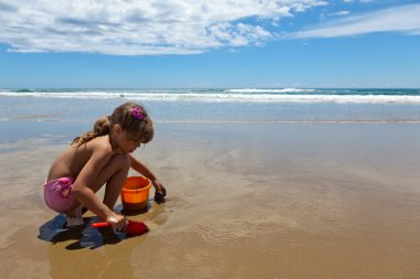 A girl playing on the wet sand with a shovel and pail