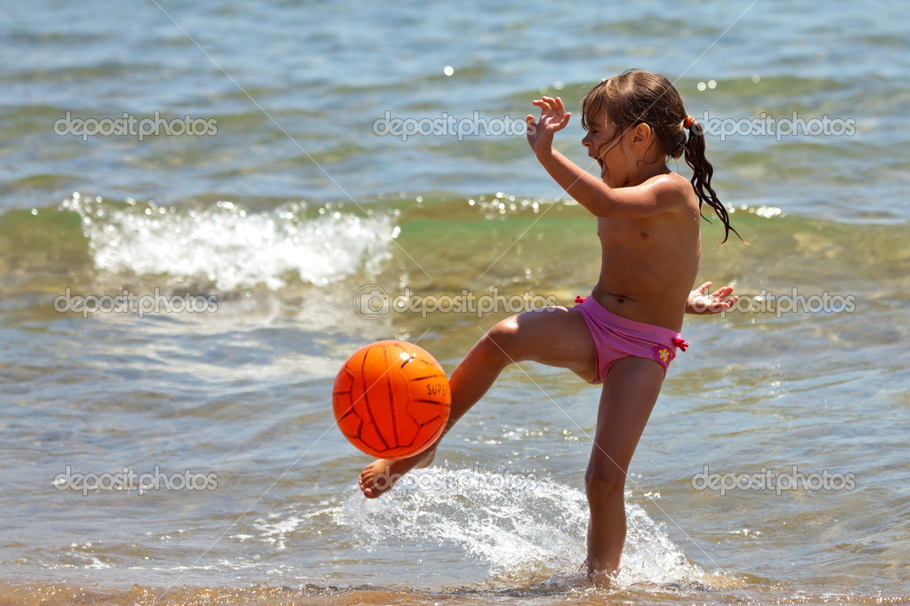 The little girl on the beach hit the ball