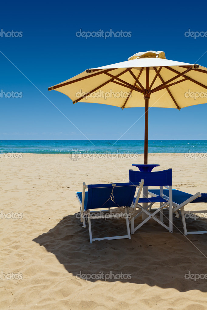 Deck chairs under an umbrella in the sand