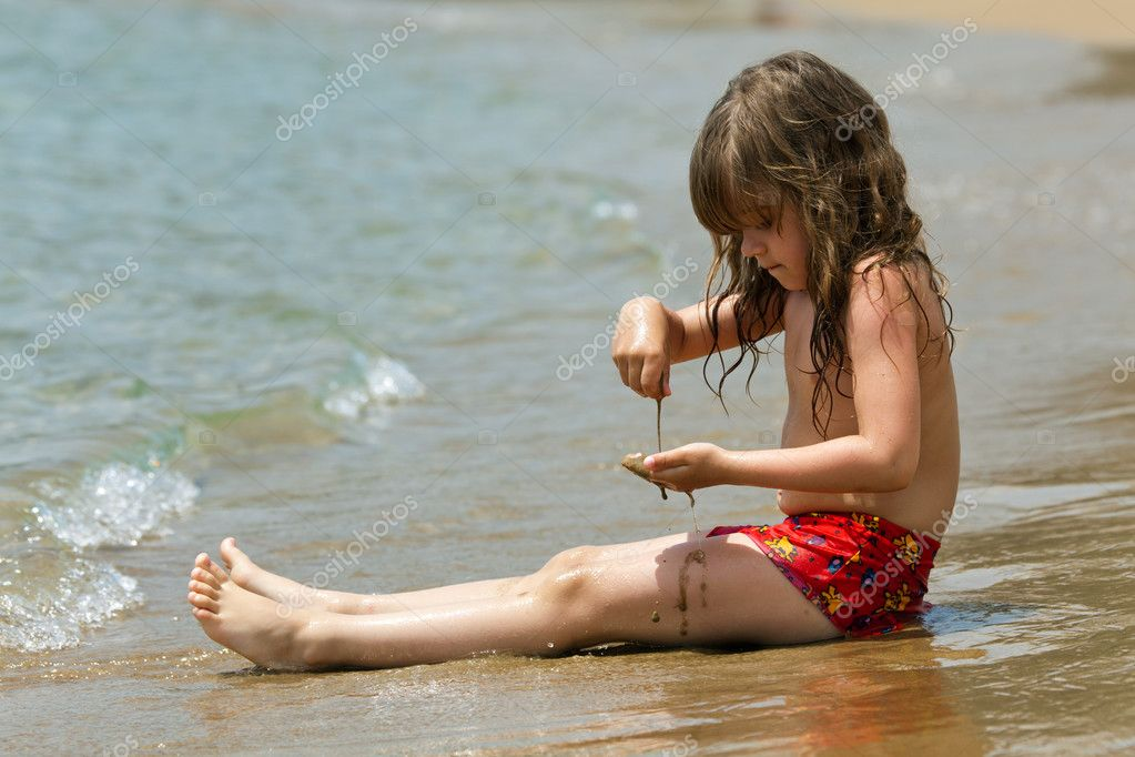 The little girl is sitting on a beach in the waves