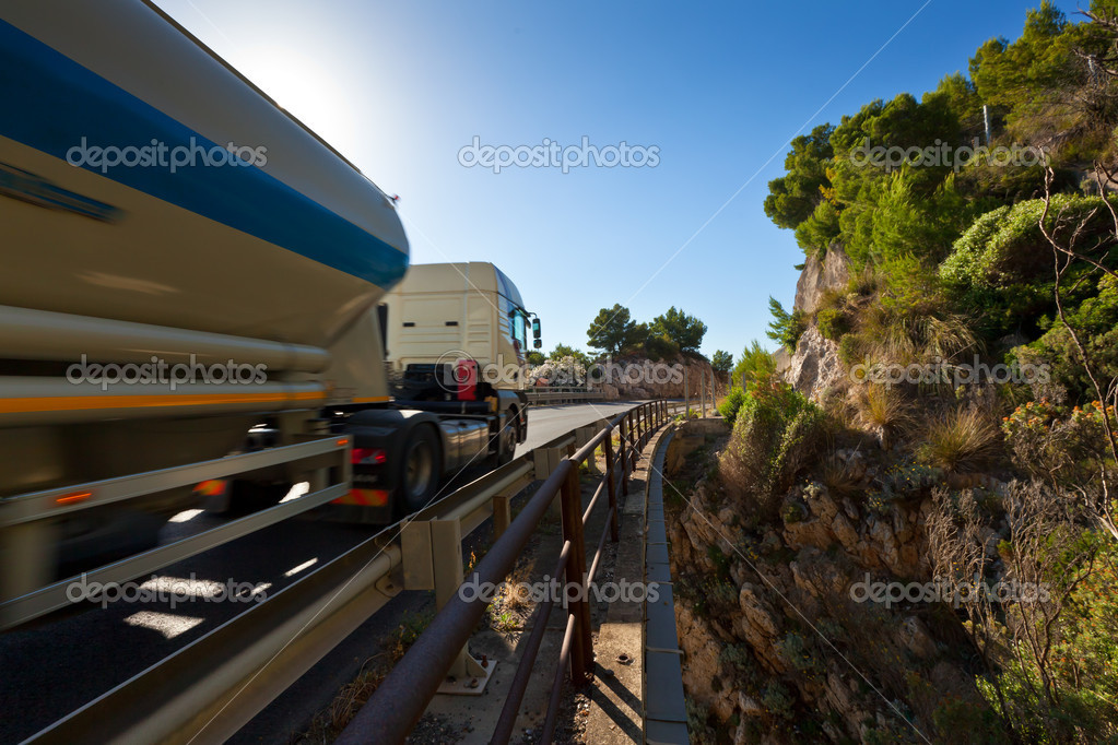 The modern truck driving fast on mountain bridge